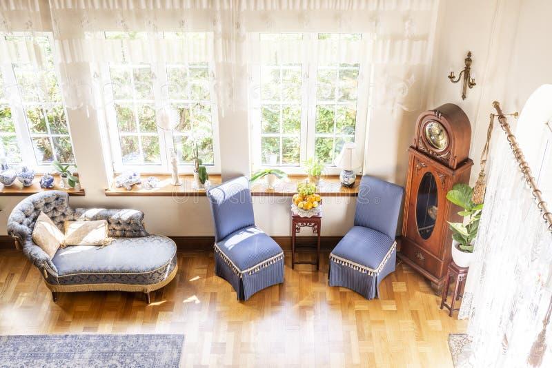 Wysoki kąt srebny hol, błękitów krzesła i drewniany zegarowy stan, obrazy royalty free