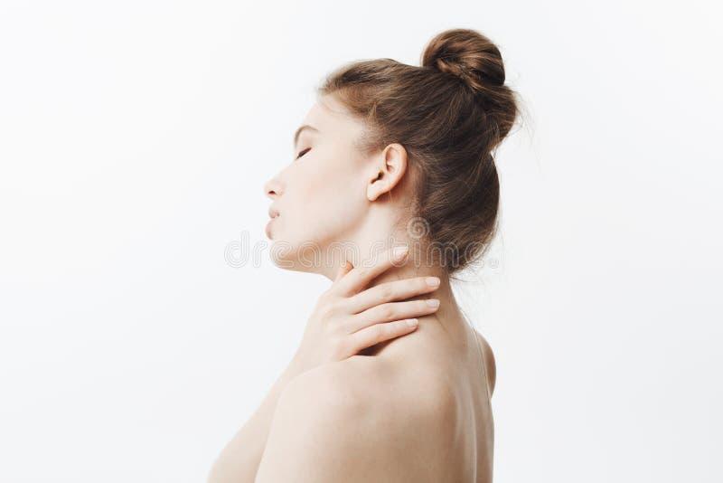 Wysoki klucz Oszałamiająco atrakcyjna caucasian młoda kobieta z ciemny długie włosy w babeczki uczesania mienia szyi z rękami, kr fotografia royalty free
