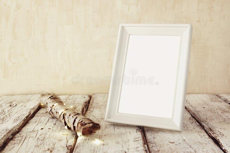 Wysoki kluczowy wizerunek stara drzewna bela z czarodziejskimi bożonarodzeniowe światła i pustą fotografii ramą na drewnianym sto obrazy royalty free