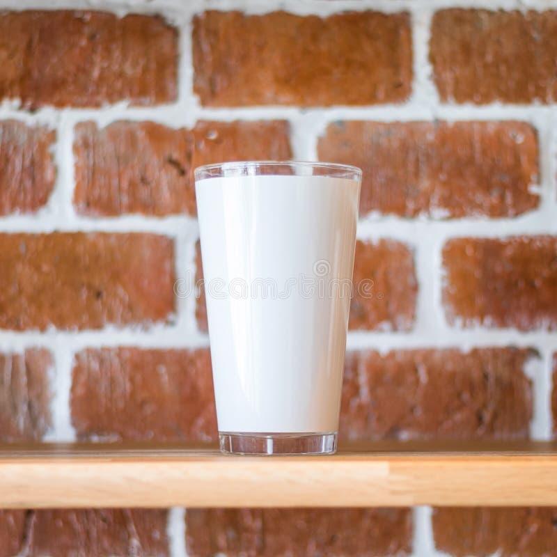 Wysoki kubek na rocznik ściany z cegieł tle Drewniana pokaz półka dla pokazywać przejrzystą napój filiżankę w grunge pojęciu bric obrazy stock