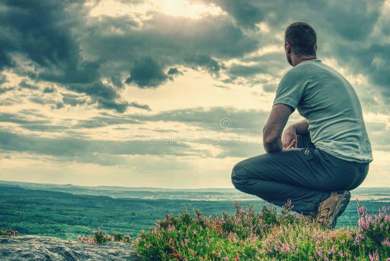 Wysoki mężczyzna siedzi na zboczu w wrzosu krzaku fotografia royalty free