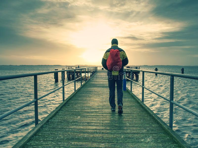 Wysoki mężczyzna w ciepłej kurtce czarnych spodniach i jest chodzący na nabrzeżu i patrzeć morze Drewniany molo na brzeg morze obraz royalty free