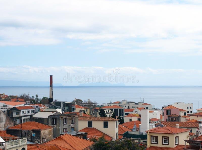 wysoki nabrze?ny widok domy z czerwonymi kafelkowymi dachami i starym fabrycznym kominem w mie?cie Funchal z niebieskim niebem z  zdjęcia royalty free