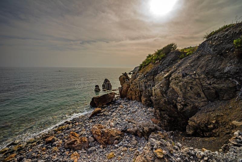 Wysoki skalisty wybrzeże i denne fale morze śródziemnomorskie zdjęcia royalty free