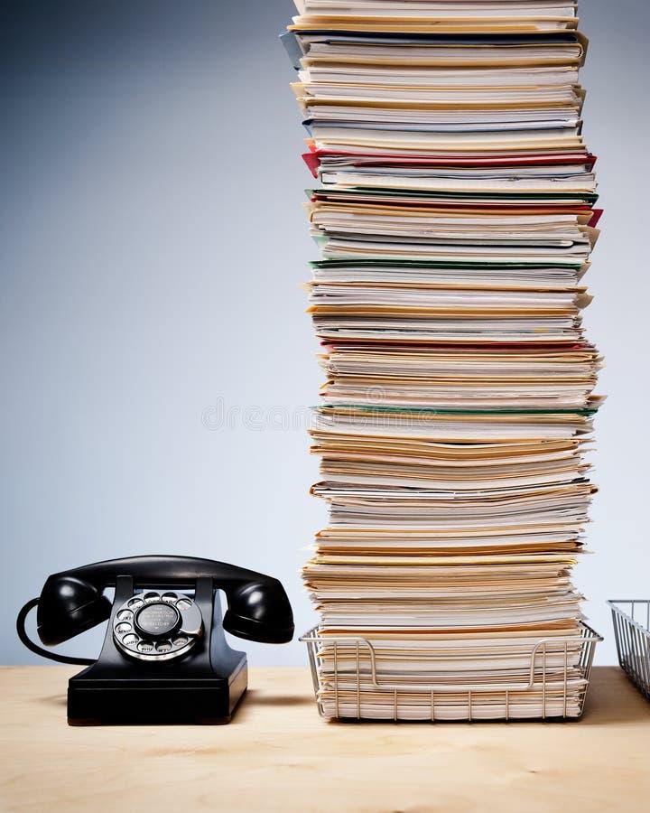 Wysoki stos kartoteki i papierkowa robota na biurku z telefonem fotografia royalty free