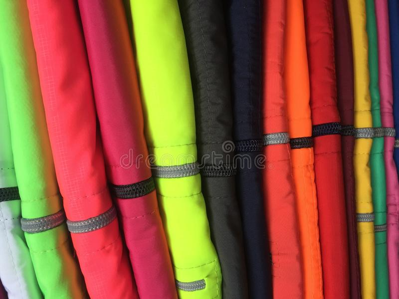 Wysoki stos kurtki z i suwaczek w środku wiele jaskrawymi, fluoriscent kolorami, zdjęcia royalty free