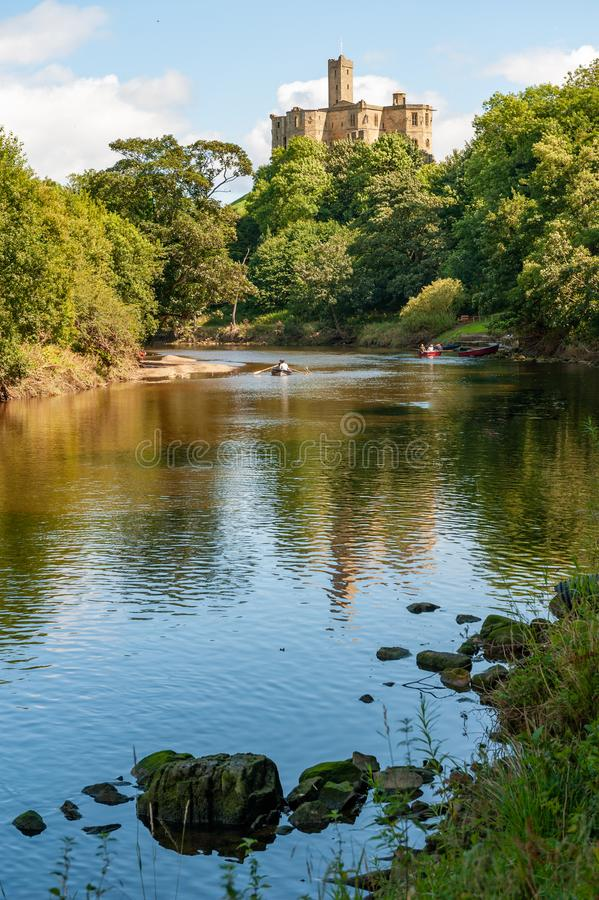 Wysoki strzał łodzi wioślarskich na rzece Coquet z Zamkiem Warkworth w tle obraz royalty free