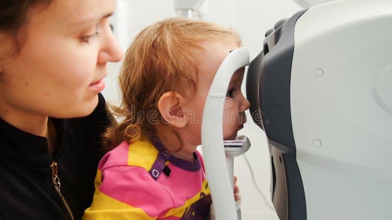 Wysoki tehnology w opiece zdrowotnej dziecka ` s okulistyka - optometrist sprawdza małej dziewczynki ` s wzrok w klinice - zdjęcie royalty free