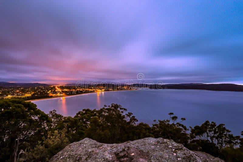 Wysoki widok oceanu i miasta noc zaświeca przeciw chmurnemu wschodowi słońca zdjęcia stock