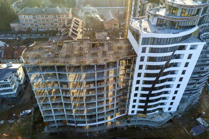 Wysoki wielo- piętrowy nowożytny mieszkanie lub budynek biurowy z błyszczącymi okno i niedokończonym budynkiem w budowie fotografia stock