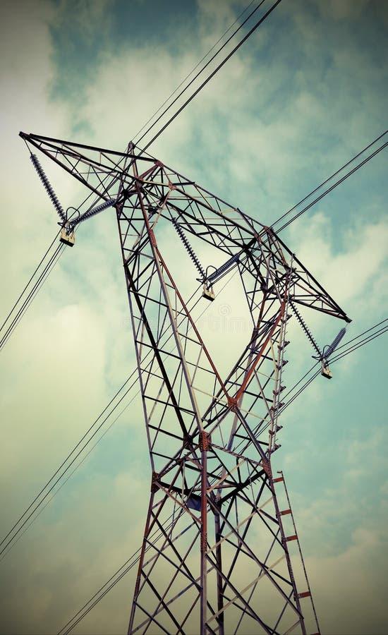 Wysoki woltażu pilon z elektrycznymi kablami i błękitnym wky obraz royalty free