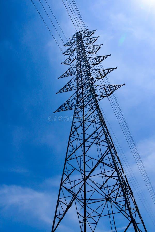 Wysoki woltażu wierza, elektryczności poczta, Elektryczna poczta na głębokim niebieskiego nieba tle obrazy stock