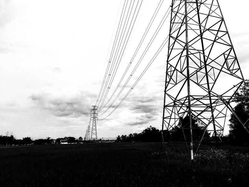 Wysoki woltażu zasilania elektrycznego słup z różnorodnym drutowaniem przez ryżu pola fotografia stock