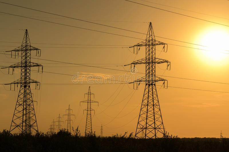 Wysokie woltażu przekazu linie przy zmierzchem Energia i elektryfikacja fotografia stock