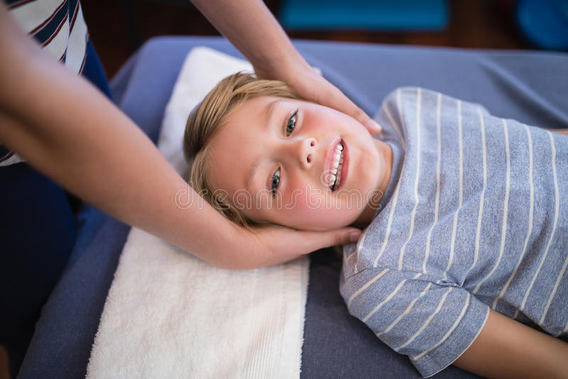 Wysokiego kąta portret uśmiechnięty uśmiechnięty chłopiec dostawania masaż od żeńskiego terapeuta zdjęcie royalty free