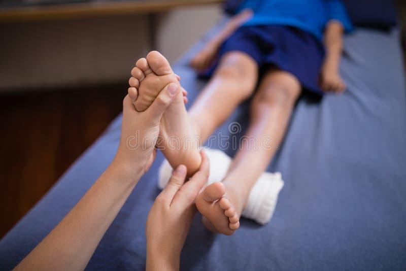 Wysokiego kąta widok chłopiec lying on the beach na łóżkowym odbiorczym nożnym masażu od żeńskiego terapeuta zdjęcia royalty free
