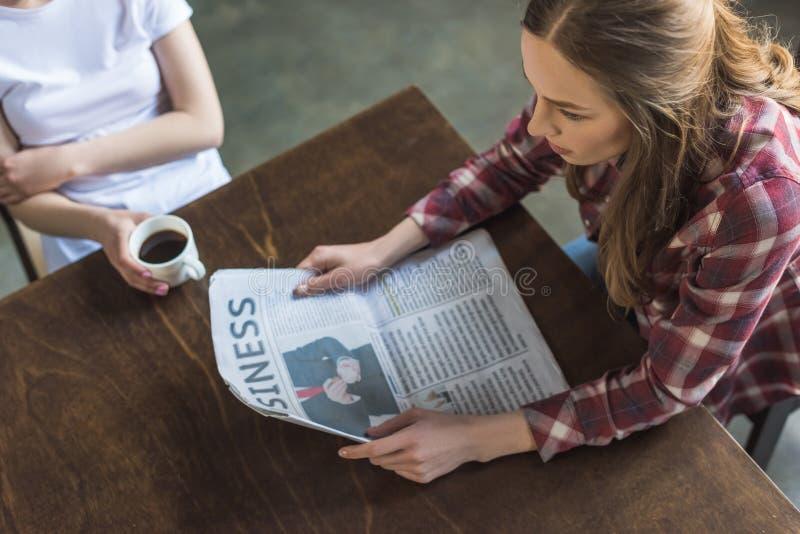 wysokiego kąta widok gazetowy kobiety czyta i pije kawę zdjęcia stock