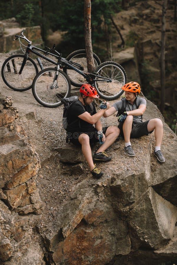 wysokiego kąta widok młodzi próbni rowerzyści relaksuje na skalistej falezie po przejażdżki i chwiania obrazy stock