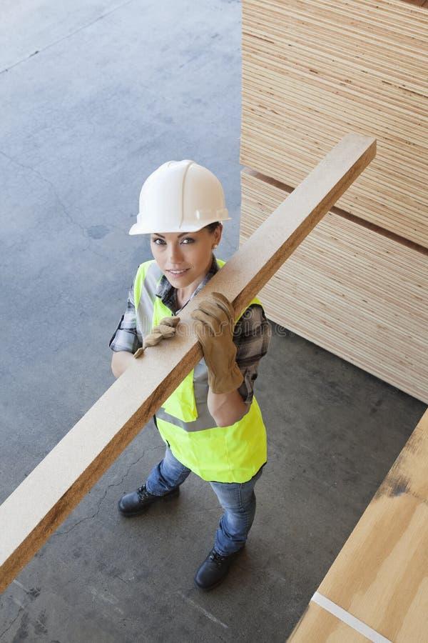 Wysokiego kąta widok niesie drewnianą deskę na ramieniu żeński pracownik fotografia stock