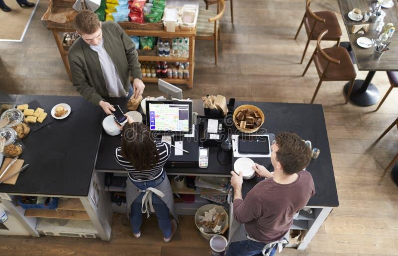 Wysokiego kąta widok płaci nad kontuarem przy sklep z kawą mężczyzna zdjęcia royalty free