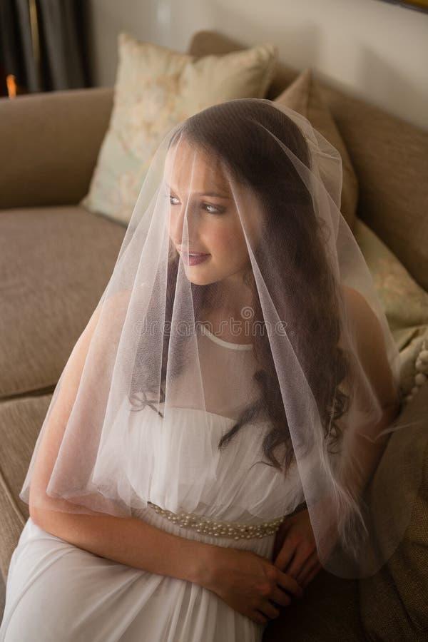 Wysokiego kąta widok piękna panna młoda w ślubnej sukni obsiadaniu na kanapie obrazy royalty free