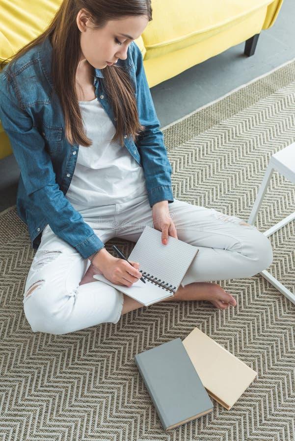 wysokiego kąta widok pisze w notatniku na dywanie i studiować dziewczyna podczas gdy siedzący fotografia royalty free