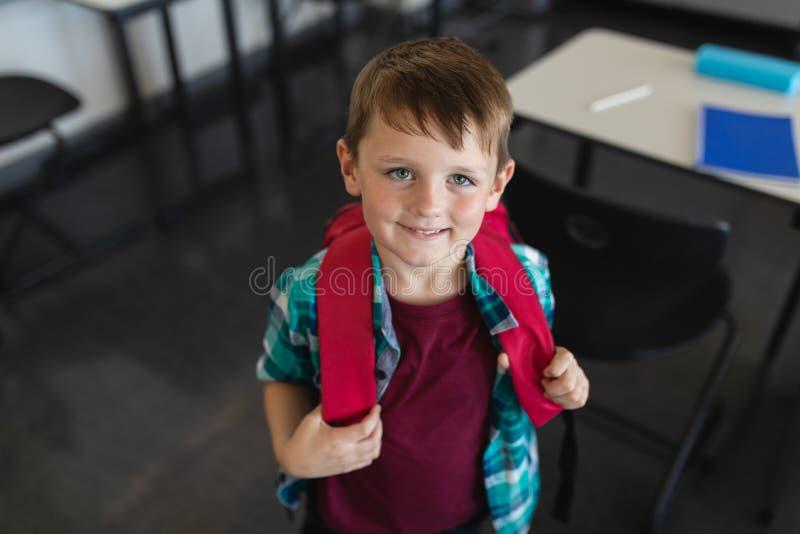 Wysokiego kąta widok szczęśliwy uczeń patrzeje kamerę w sali lekcyjnej z schoolbag zdjęcie royalty free
