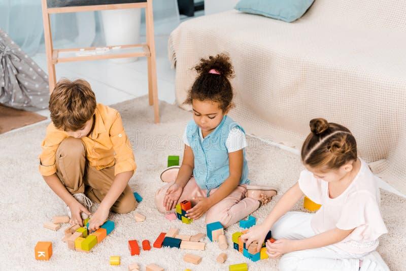 wysokiego kąta widok uroczy multiracial dzieci bawić się z kolorowymi sześcianami obrazy royalty free