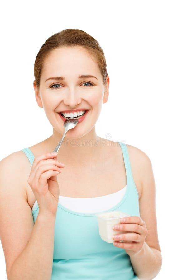 Wysokiego kluczowego portreta kobiety łasowania młody caucasian jogurt odizolowywający obraz stock