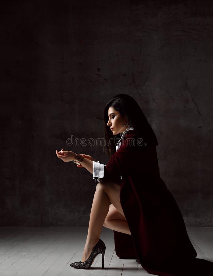Wysokiego społeczeństwa kobiety elegancka brunetka w czarnej kurtce i białym koszulowym siedzącym puszku przymocowywać bransoletk obrazy royalty free