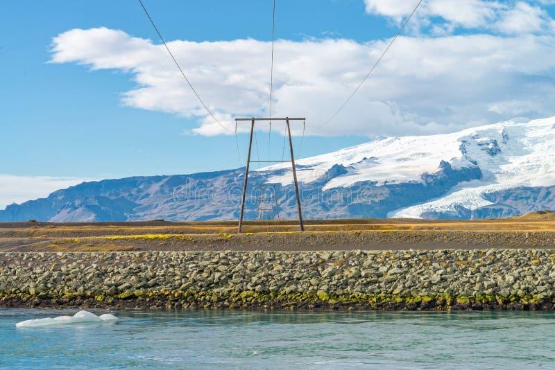 Wysokiego woltażu elektryczni słupy lokalizować w wsi, Iceland zdjęcie stock