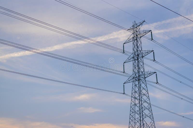 Wysokiego woltażu elektryczni słupy z jasnym niebem fotografia royalty free