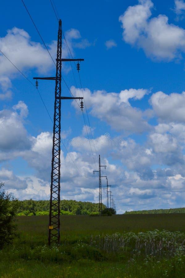Wysokiego woltażu elektryczny przekaz góruje i linie energetyczne na polu zdjęcie stock