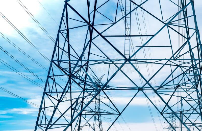 Wysokiego woltażu elektryczny wierza i przekaz linie Elektryczność pilony z niebieskiego nieba i bielu chmurami W?adza i energia zdjęcie stock