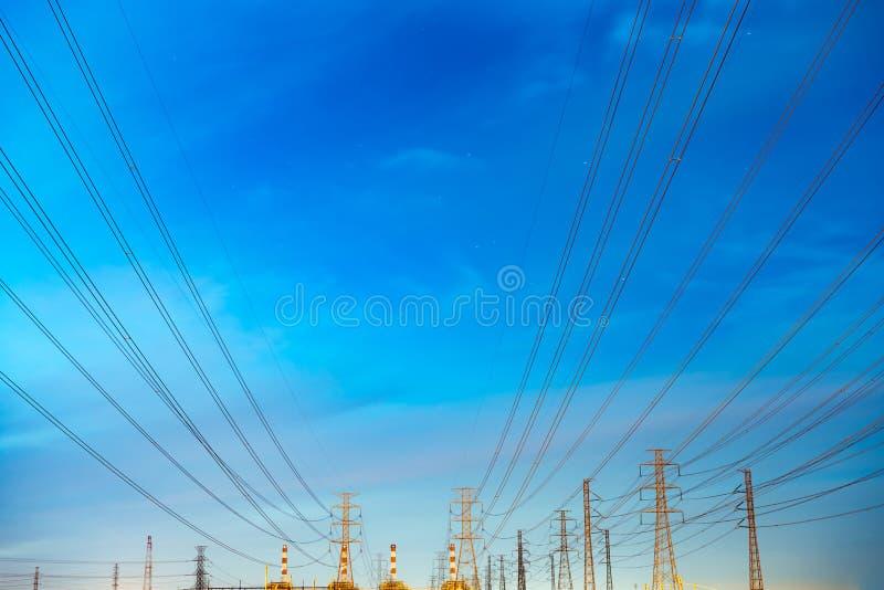 Wysokiego woltażu przekazu i słupa elektryczne linie w wieczór Elektryczność pilony przy nocą Władza i energia Energia fotografia royalty free