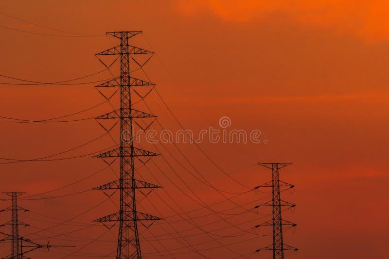 Wysokiego wolta?u przekazu i s?upa elektryczne linie w wiecz?r Przy zmierzchem elektryczno?? pilony W?adza i energia Energia fotografia royalty free