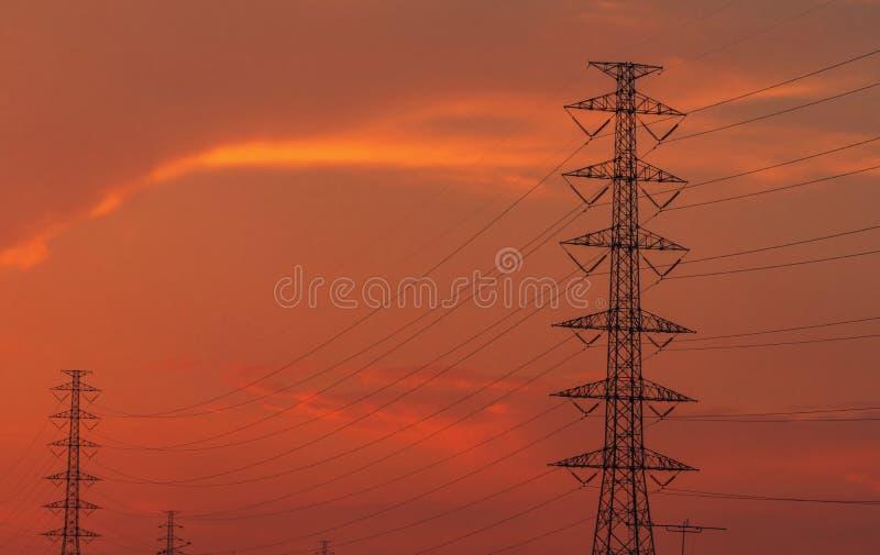 Wysokiego wolta?u przekazu i s?upa elektryczne linie w wiecz?r Przy zmierzchem elektryczno?? pilony W?adza i energia Energia zdjęcie royalty free