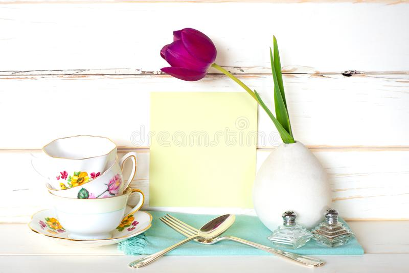 Wysokiej herbaty czas z stertą Kolorowi Teacups Purpurowy tulipan w wazie, rozwidlenie i łyżka, z jasnozieloną menu kartą na Biał fotografia royalty free
