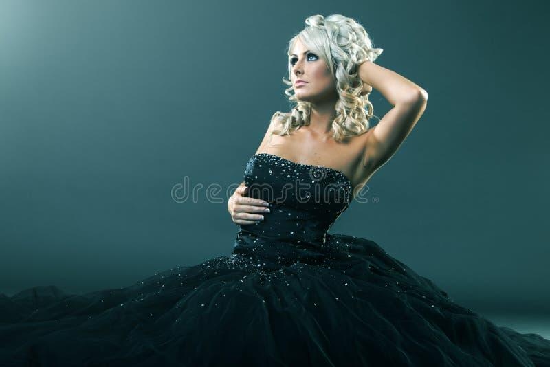 Wysokiej mody kobieta w seksownej pozie i wielkim formalnej sukni obsiadaniu zdjęcia royalty free