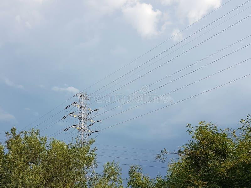 Wysokonapięciowa linia energetyczna iluminująca światłem słonecznym przeciw tłu chmury burzowy niebo Transport energia nad długim obraz royalty free