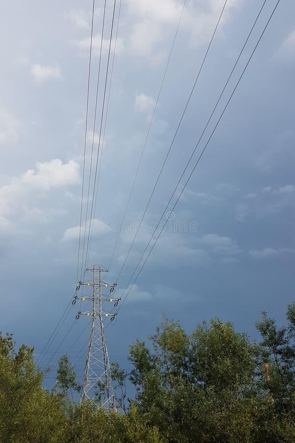 Wysokonapięciowa linia energetyczna iluminująca światłem słonecznym przeciw tłu chmury burzowy niebo Transport energia nad długim obrazy royalty free