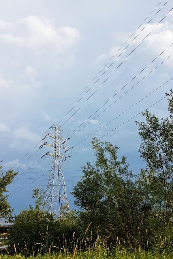 Wysokonapięciowa linia energetyczna iluminująca światłem słonecznym przeciw tłu chmury burzowy niebo Transport energia nad długim fotografia royalty free