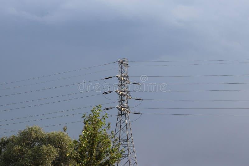 Wysokonapięciowa linia energetyczna iluminująca światłem słonecznym przeciw tłu chmury burzowy niebo Transport energia nad długim zdjęcia royalty free