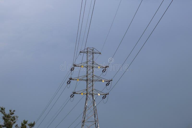 Wysokonapięciowa linia energetyczna iluminująca światłem słonecznym przeciw tłu chmury burzowy niebo Transport energia nad długim zdjęcie stock