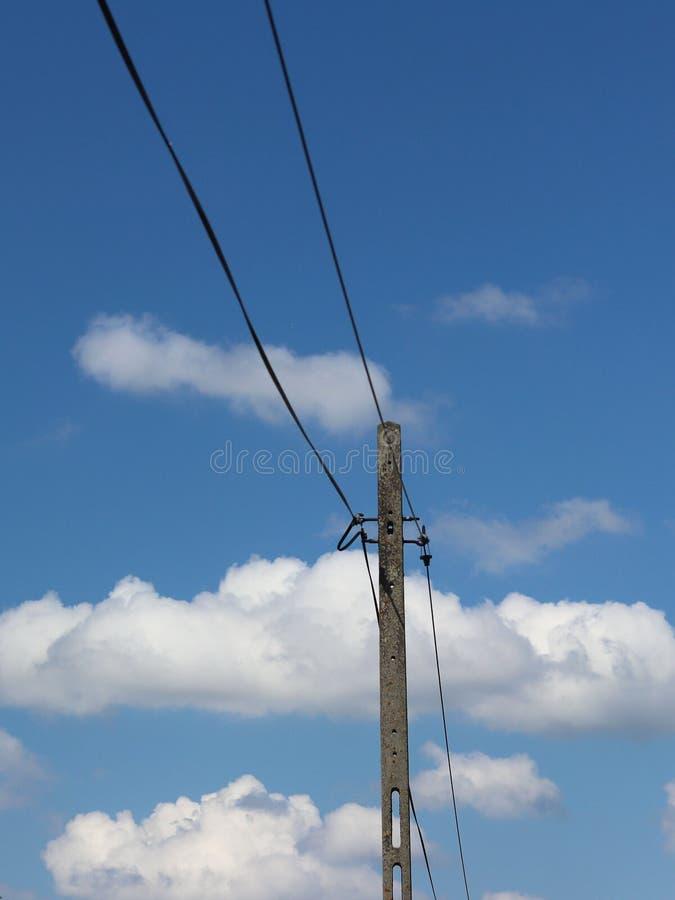 Wysokonapięciowa linia energetyczna iluminująca światłem słonecznym przeciw tłu chmury burzowy niebo Transport energia nad długim obraz stock