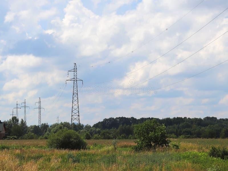 Wysokonapięciowa linia energetyczna iluminująca światłem słonecznym przeciw tłu chmury burzowy niebo Transport energia nad długim zdjęcia stock