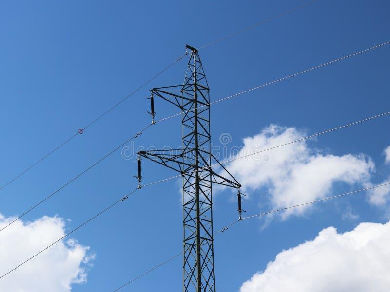 Wysokonapięciowa linia energetyczna iluminująca światłem słonecznym przeciw tłu chmury burzowy niebo Transport energia nad długim zdjęcie royalty free