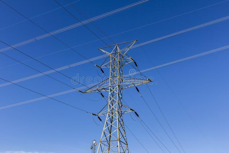 Wysokonapięciowe linie energetyczne i pilon przeciw niebieskiemu niebu II zdjęcie stock