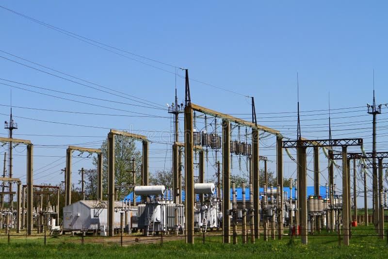 Wysokonapięciowe linie energetyczne i woltaży transformatorowi bloki na niebieskim niebie podstacja energii elektrycznej zdjęcia stock