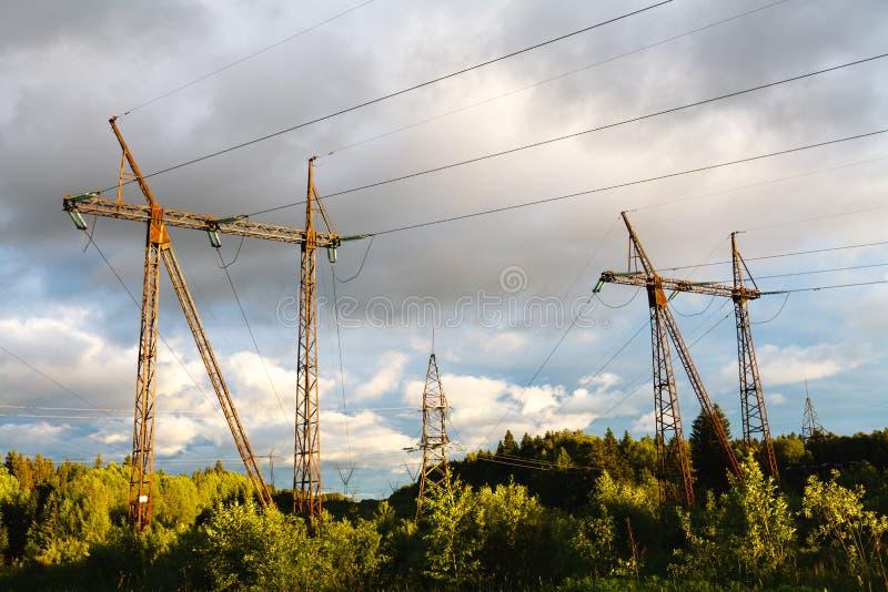 Wysokonapięciowe linie energetyczne przy zmierzchem elektryczności dystrybuci sta fotografia royalty free